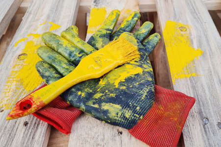 Black work protective gloves and paint brush smeared with yellow painted lies on a wooden pallet.