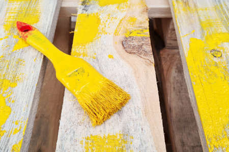 Paint brush painted with yellow color lie on a wooden pallet. Stock Photo