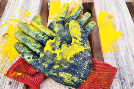 Pair of black work protective gloves painted in yellow lie on a wooden pallet.