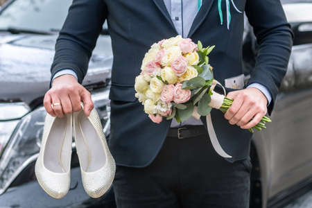 Groom dressed in blue suit holding a bridal bouquet of roses and white female wedding shoes on a car background.