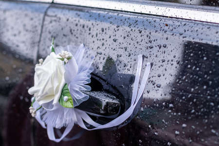 Faux rose boutonniere decorates a car door handle in the rain.