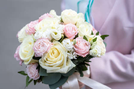 Bride holding bridal bouquet of roses outdoors.
