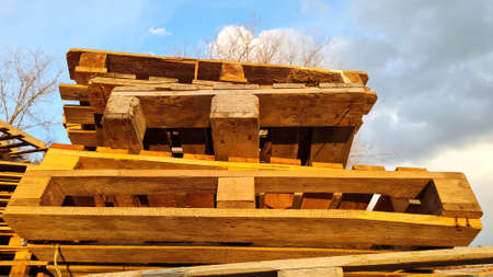 Stack of Old Used Wooden pallets outdoors in the warehouse of cargo delivery enterprise on a cloudy sky background, upper view. Stock Photo