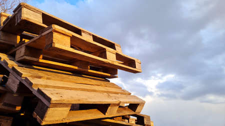Group of Old Used Wooden pallets is stack outdoors in the warehouse of cargo delivery enterprise on a cloudy sky background, copy space.