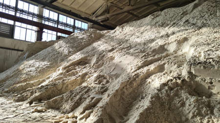 Pile of ammonium sulfate powder inside a warehouse of chemical plant. Mineral organic fertilizers for agriculture industry.