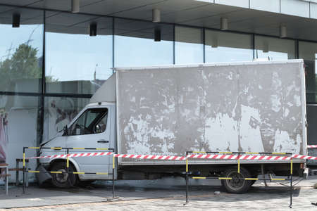 White lorry collided with a glass wall of shopping mall. Accident site is isolated and fenced off with a signal tape.