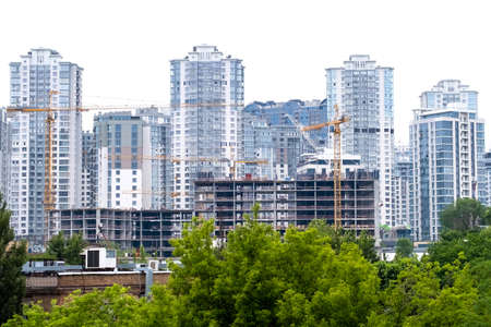 Cranes on a construction site of building of modern residential district High apartment buildings or skyscrapers in a new elite complex. Stock Photo