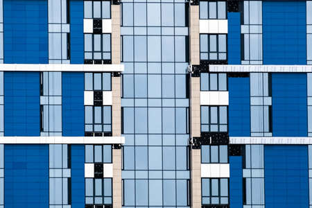 Close-up of many windows on a blue exterior of modern apartment building. For real estate Background. Stock Photo