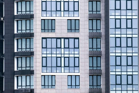 Closeup of many windows on a gray facade of modern apartment building. For real estate Background. Stock Photo