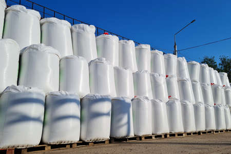 Group of white big bags with chemical fertilizers in a warehouse outdoors. Stack of sacks in a 3 row open air on a blue sky background at sunny day.