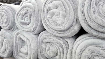 Rolled gray blankets  in a store for sale. Soft fluffy beige plaids sells in a shop shelf.