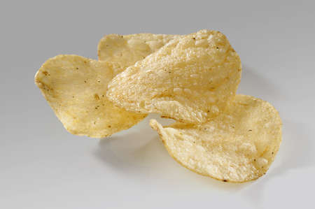 Some potato chips on the gray background Stock Photo