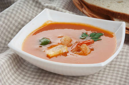 Tomato soup with shrimps and parsley in the white bowl