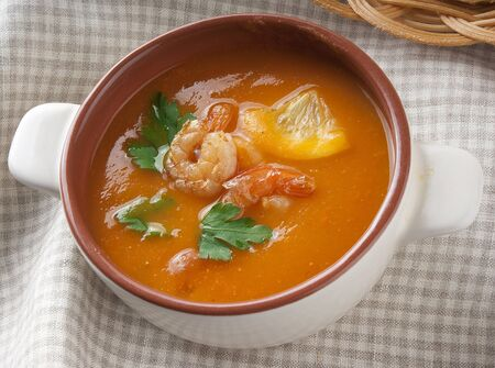 Tomato soup with shrimps, lemon and parsley in the bowl Stock Photo