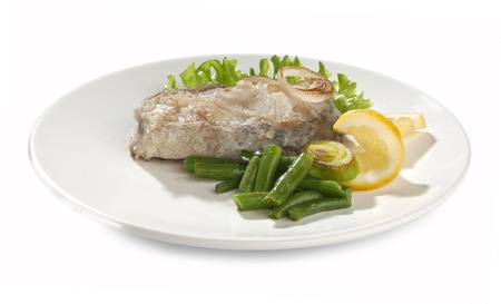 Fried piece of cod with lettuce, lemon, string beans and leek on the plate Stock Photo - 14060547