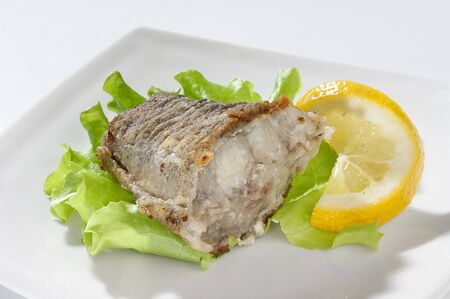 Fried piece of cod with lettuce and lemon on the plate Stock Photo - 14058782