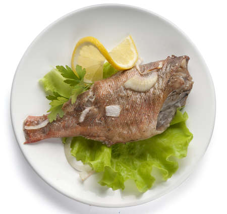 dinne: Baked rosefish with lettuce and lemon on the plate