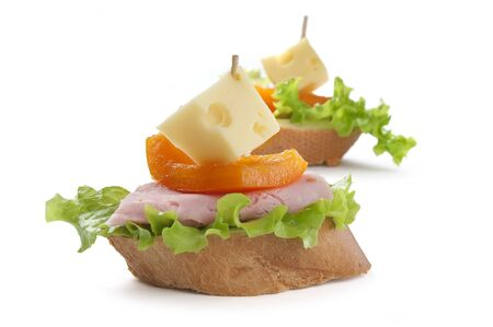 Canape with ham, paprika, lettuce and cheese on the white Stock Photo