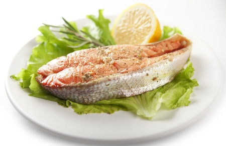 Fried trout with lettuce, lemon and rosemary on the plate photo