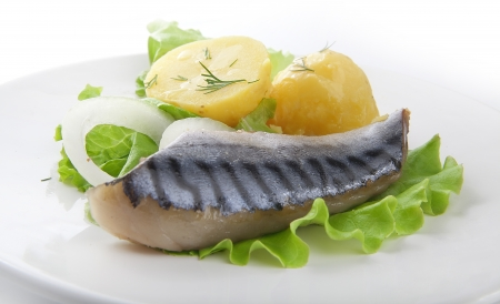 Piece of jack mackerel with boiled potato, onion and lettuce on the plate photo