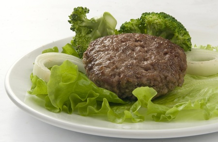 Meat rissole with broccoli, lettuce and onion on the plate photo