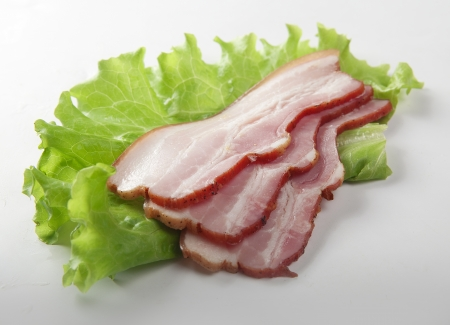 Some pieces of bacon on the green lettuce