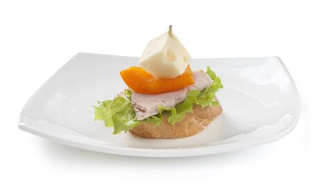 Canape with ham, paprika, lettuce and cheese on the white plate photo