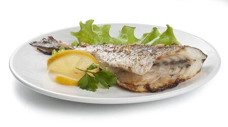 Daurade au four avec de la laitue, de citron et de persil sur la plaque blanche