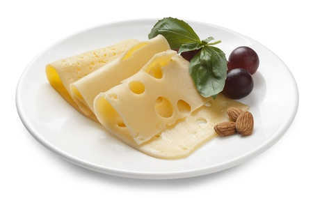 Assorted pieces of cheese with basil, almond and grape on the white plate