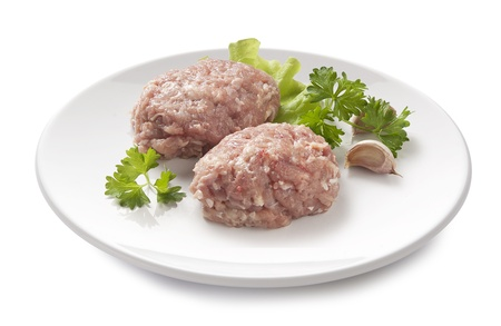 Two raw chicken rissoles with parsley, garlic and lettuce on the white plate Stock Photo - 15897767