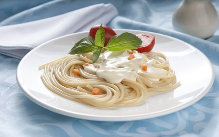 Spaghetti with cheese-cream sauce, tomato and basil on the white plate Stock Photo