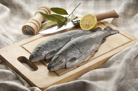Two trunk of raw trout with lemon and bay leaf on the wooden board Stock Photo - 16312463