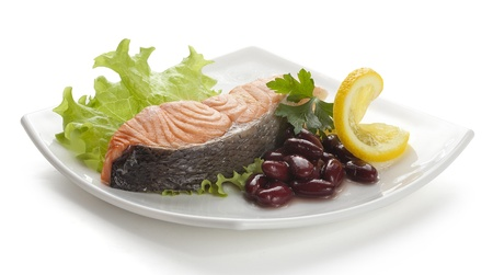 Steamed fillet of salmon with parsley, harricot, lettuce and lemon on the white plate Stock Photo
