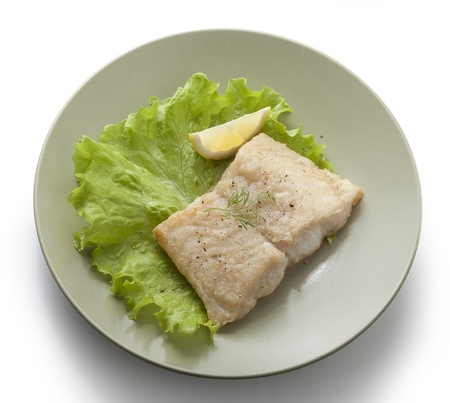 pangasius: Fried fillet of pangasius with lettuce and lemon on the green plate