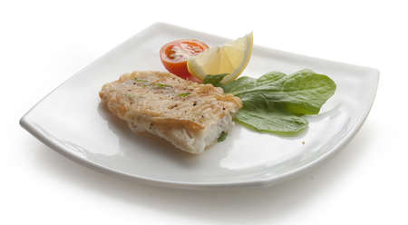 Fried fillet of tilapia with lettuce, lemon and tomato on the white plate photo