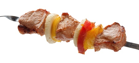 Hot roasted meat with onion, tomato and papper on the metal skewer Stock Photo