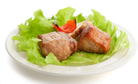 Two pieces of roasted meat with onion, paprika and fresh lettuce on the white plate Stock Photo - 19832572