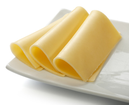 Three sliced piece of cheese on the white plate Stock Photo