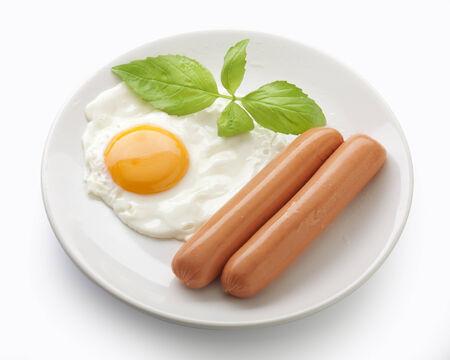 新鮮な緑のバジルと皿の上の目玉焼き 2 つ水煮ソーセージ 写真素材
