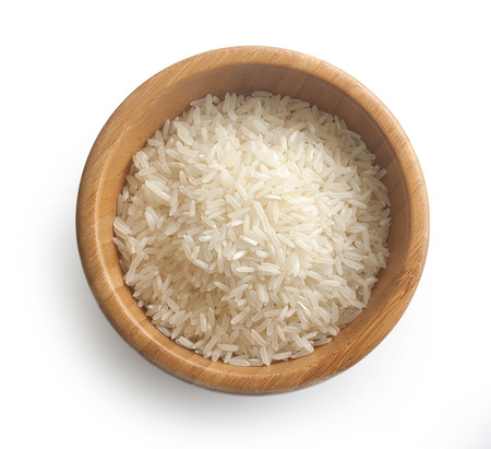 Isolated handful of raw rice in the wood bowl