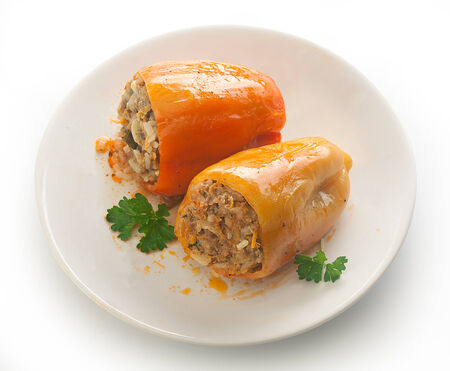 Two stuffed peppers with fresh parsley on the white plate Reklamní fotografie
