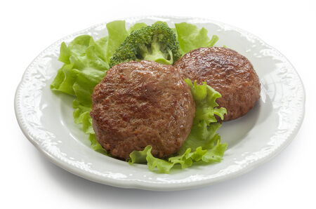 Two meat rissoles with fresn green letuce and broccoli on the white plate photo