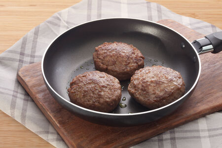 Black frying pan with three meat rissoles on the wooden board Stock Photo