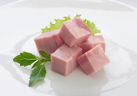 jamon: Algunas piezas de jam�n con albahaca fresca y verde en el plato Foto de archivo