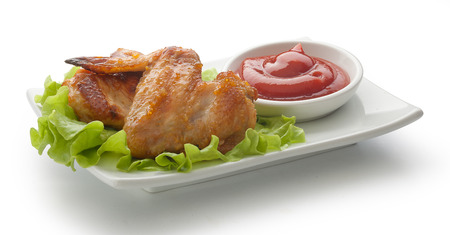 Two fried chicken wings with fresh green lettuce and red tomato sauce on the white plate Stock Photo