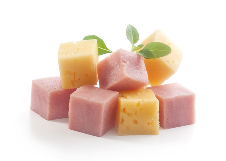 Isolated handful of ham and cheese cubes with fresh green basil Stock Photo