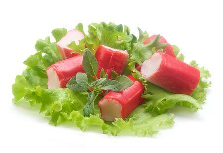 赤いカニ棒、新鮮なレタスとバジルの白いプレートの部分のサラダ