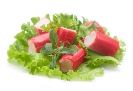 Salad with pieces of red crab stick, fresh lettuce and basil on the white plate