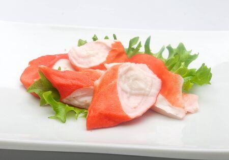 cangrejo: Algunos pedazos de carne de cangrejo, lechuga fresca en la placa blanca