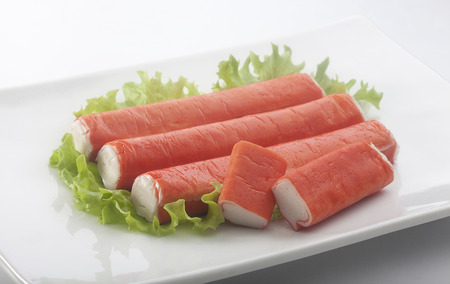 Some red crab stick with green lettuce on the white plate
